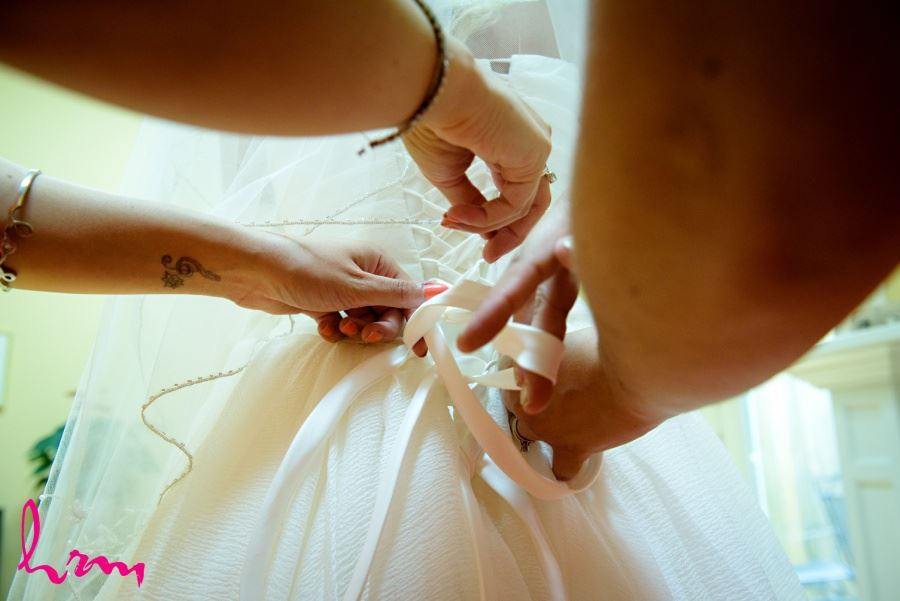 Bride getting ready lacing dress shot