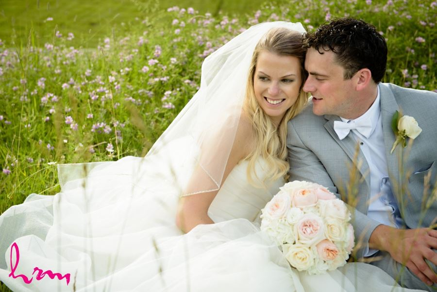 Bride and groom sitting in meadow wedding day photography